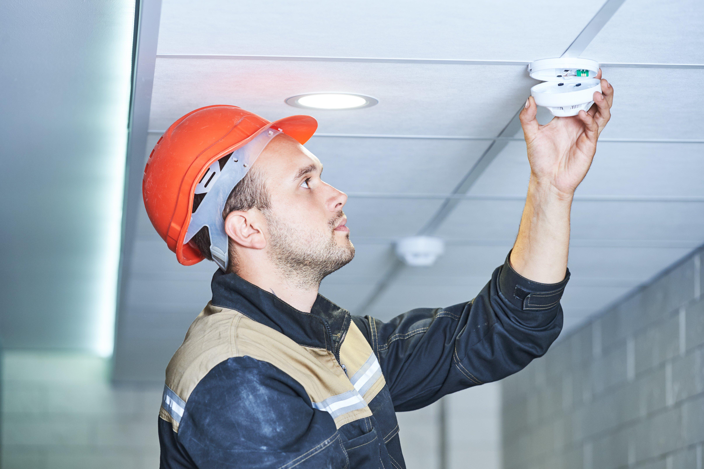 Worker fixing smoke detector