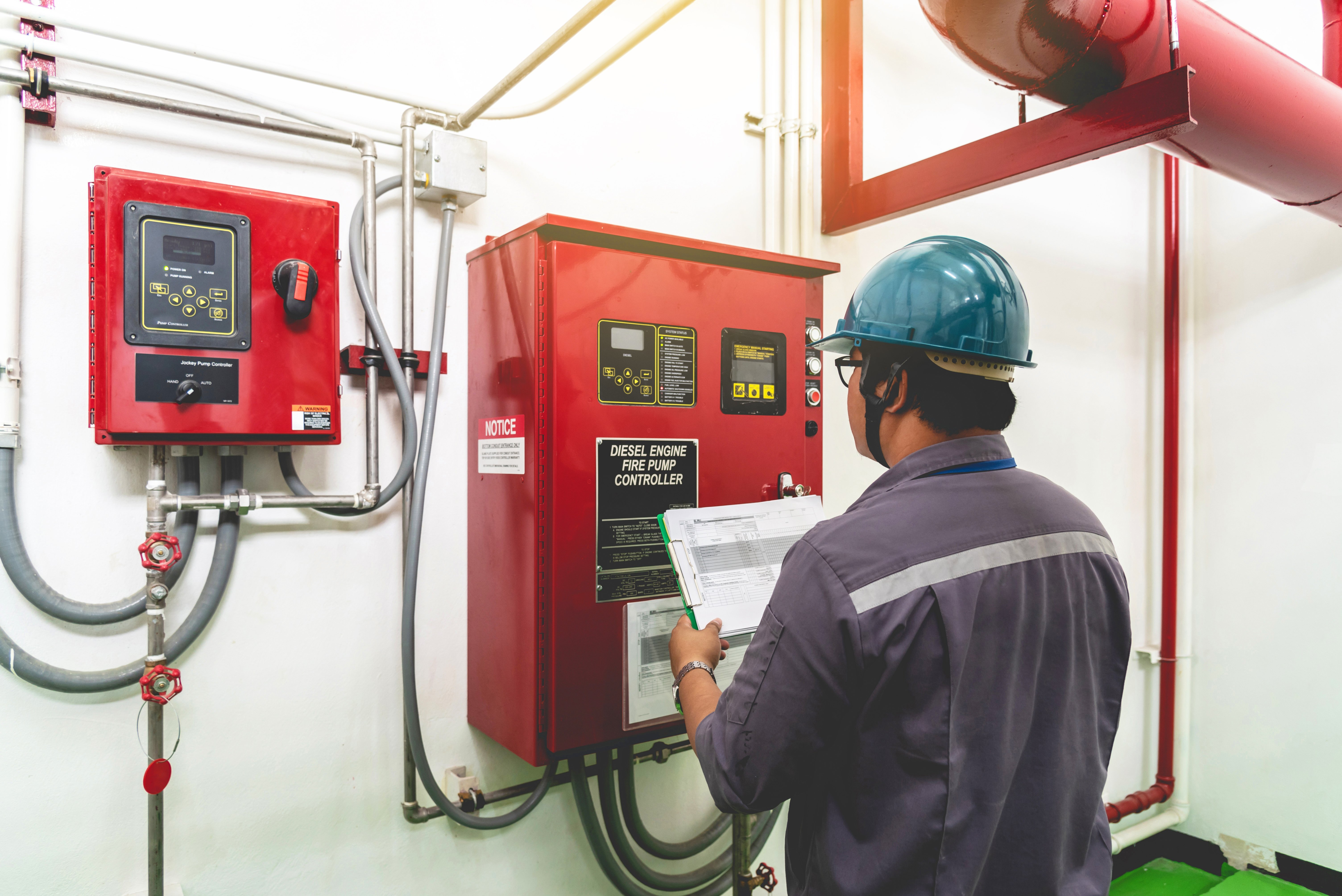 Worker looking at fire system control panel