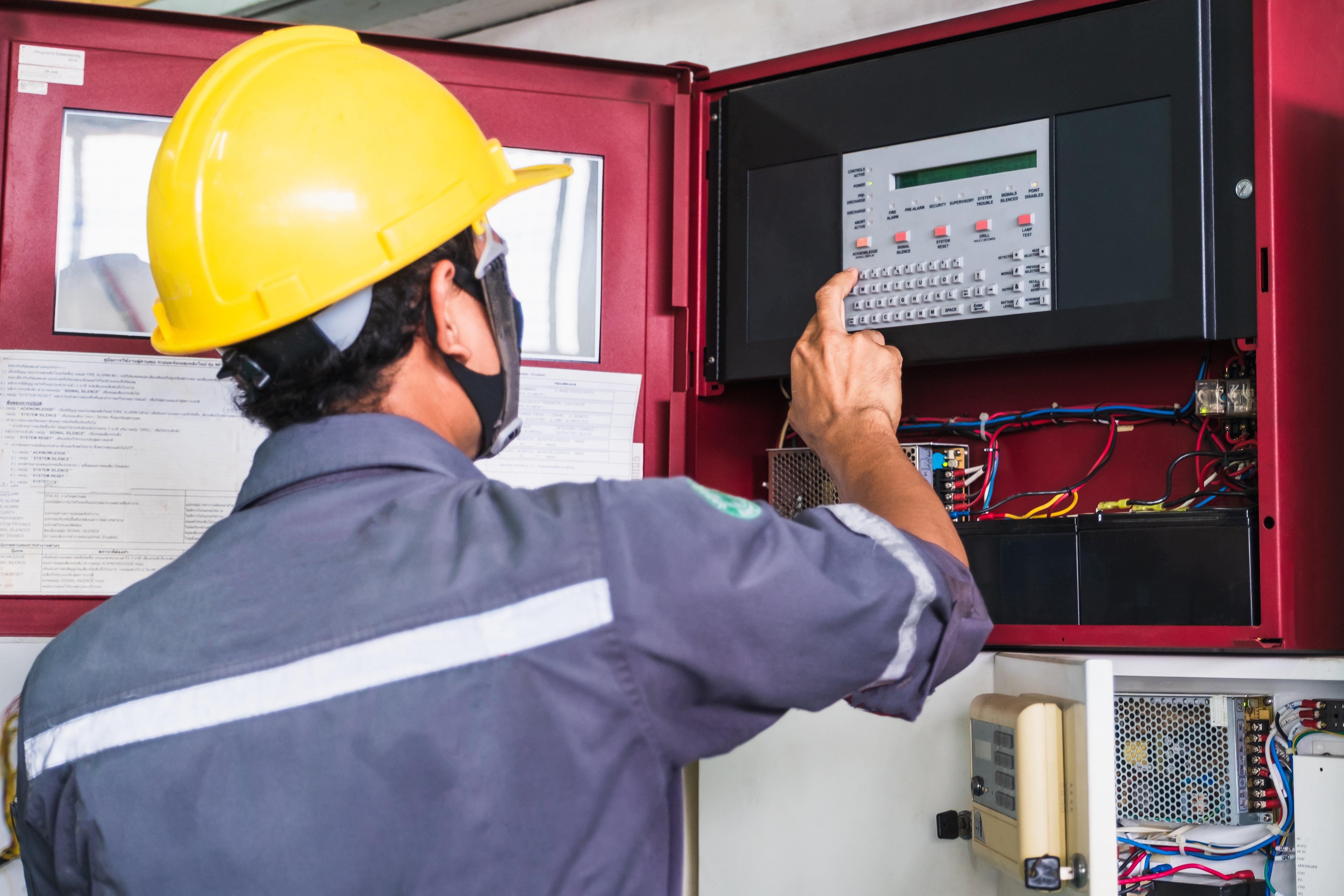 Worker technician working on fire alarm system