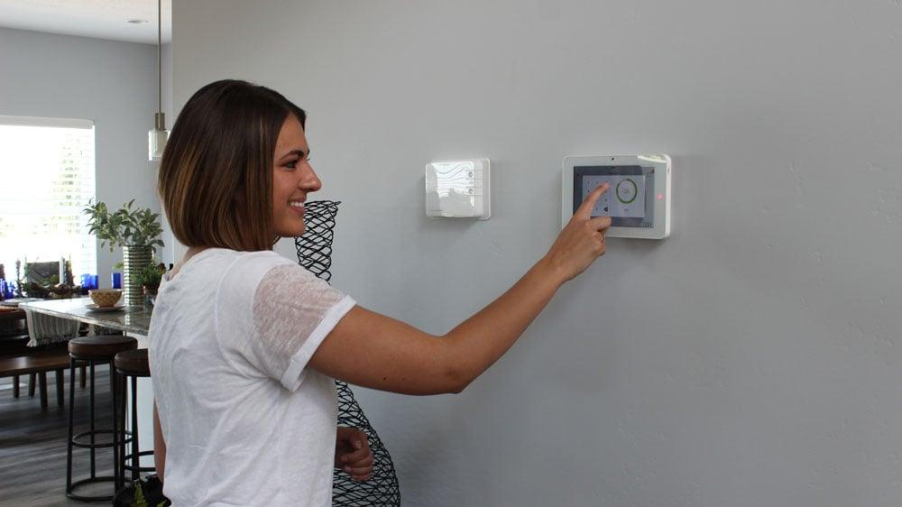 Woman using Qolsys IQ Panel in home