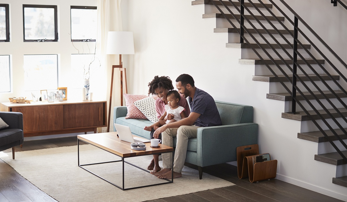 family sitting in living room setting up security devices