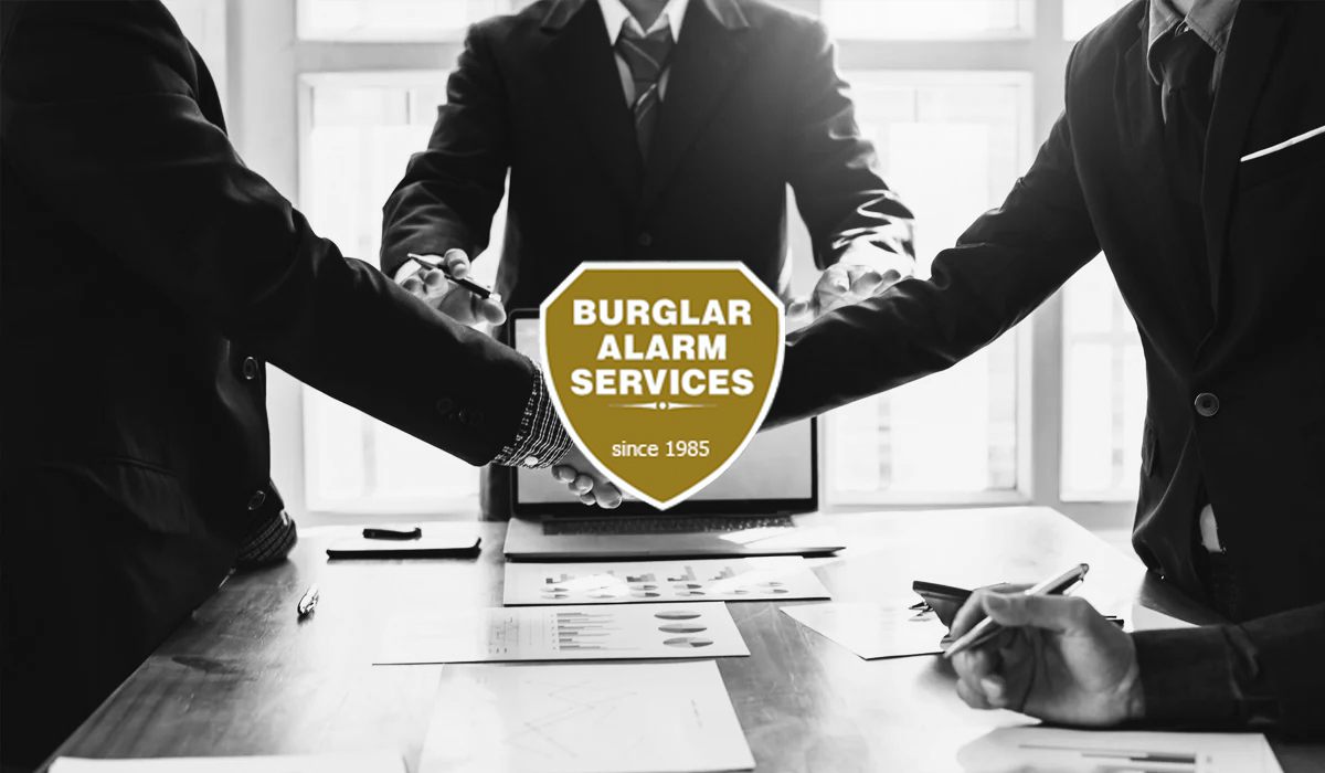 Black and white image of a business deal handshake with Burglar Alarm Services logo over top