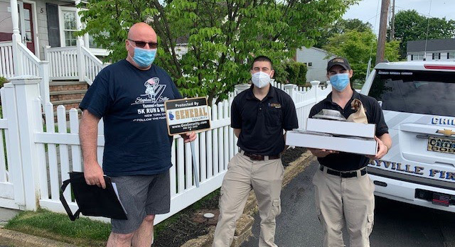 General Security employees John Doyle, Michael Minicozzi, and Alex Minicozzi deliver complimentary catered meals to hometown heroes of the Bayville Fire Department.