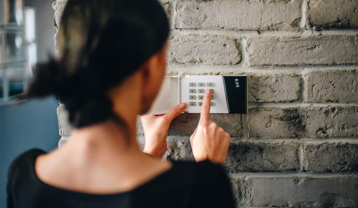 Girl entering code on alarm system