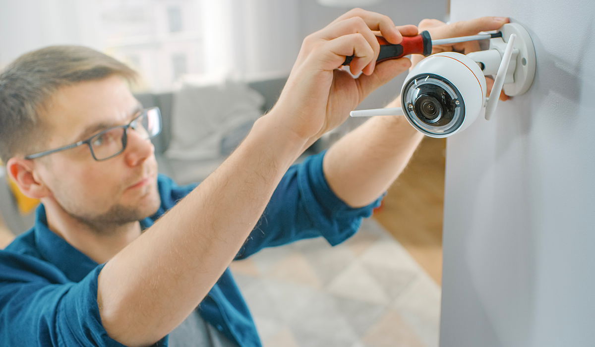 Guy with glasses and blue shirt using screwdriver to install wifi camera in brightly lit home