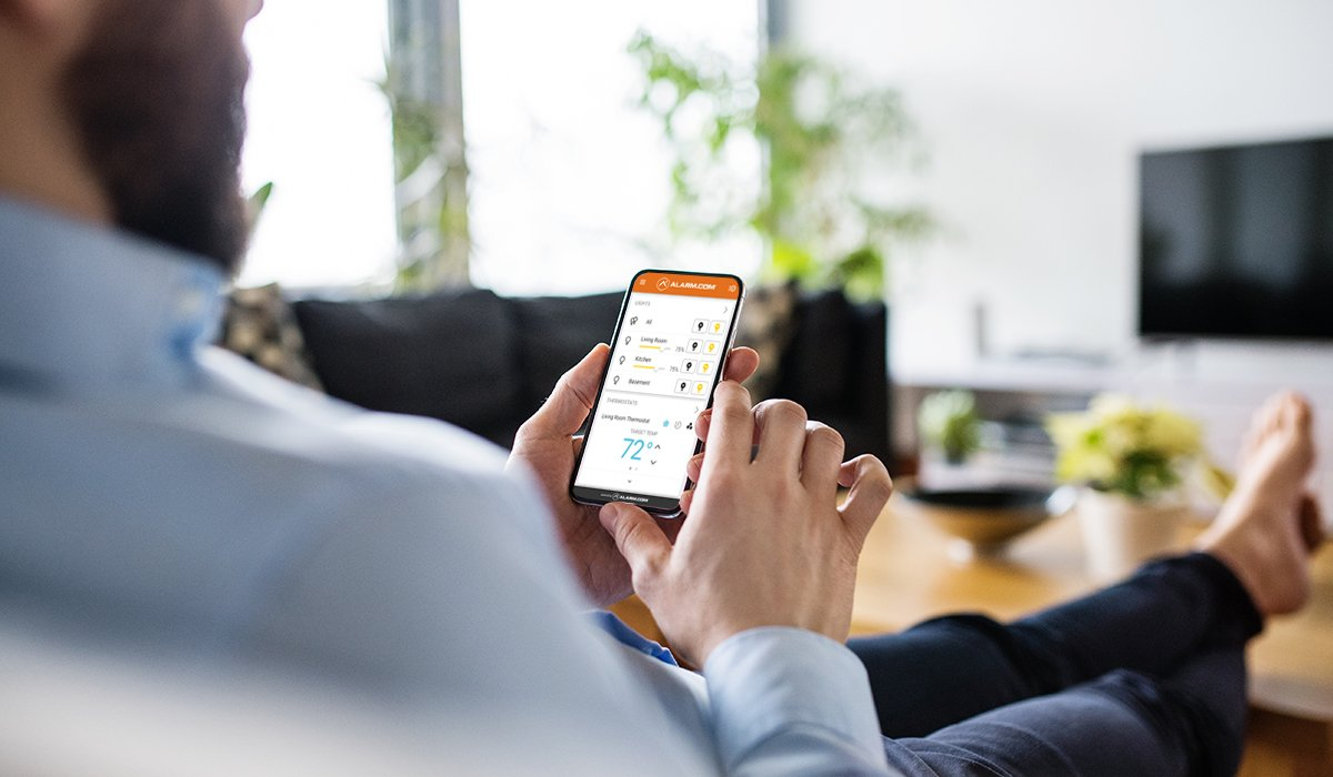 Man sitting on couch looking at smart home security app