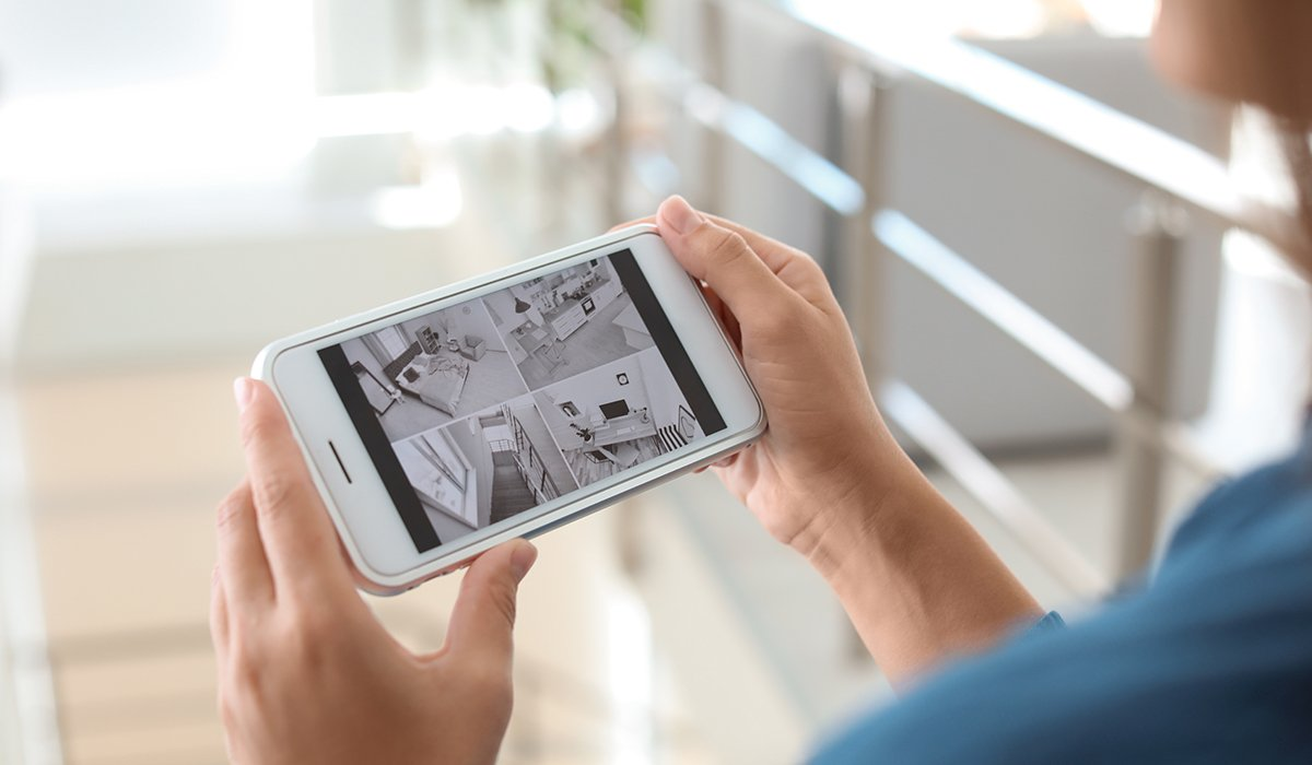 Phone user looking at security camera feed on smartphone