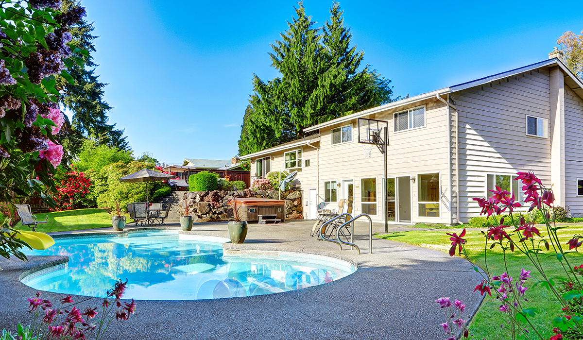 Summer home backyard with pool and basketball hoop