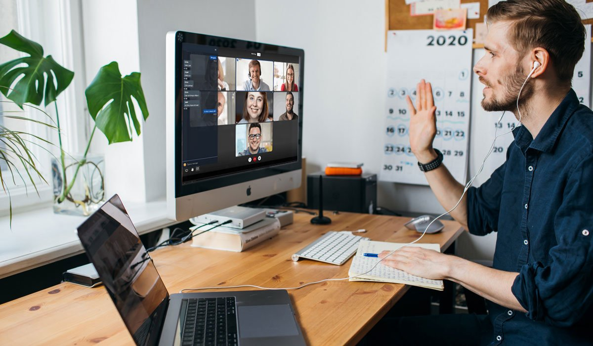 man working from home using screenshare waving at computer