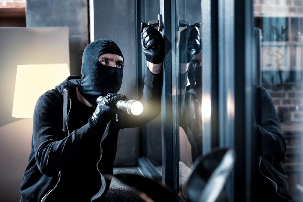 Burglar outside of home pulling on door handle with flashlight