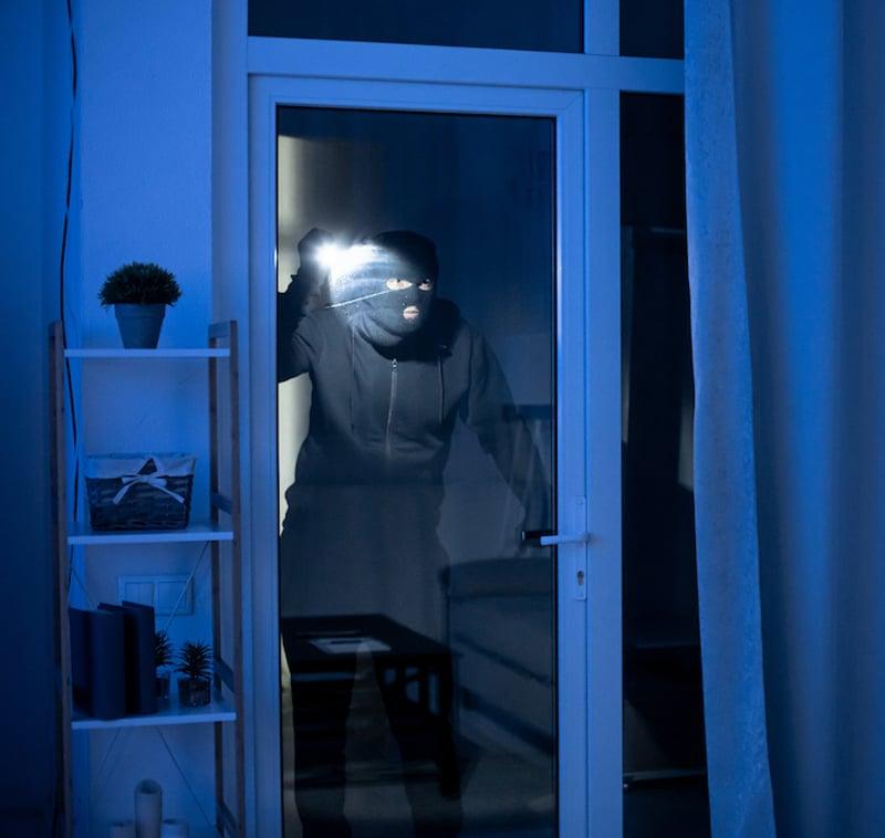 Burglar-attempting-to-break-into-house
