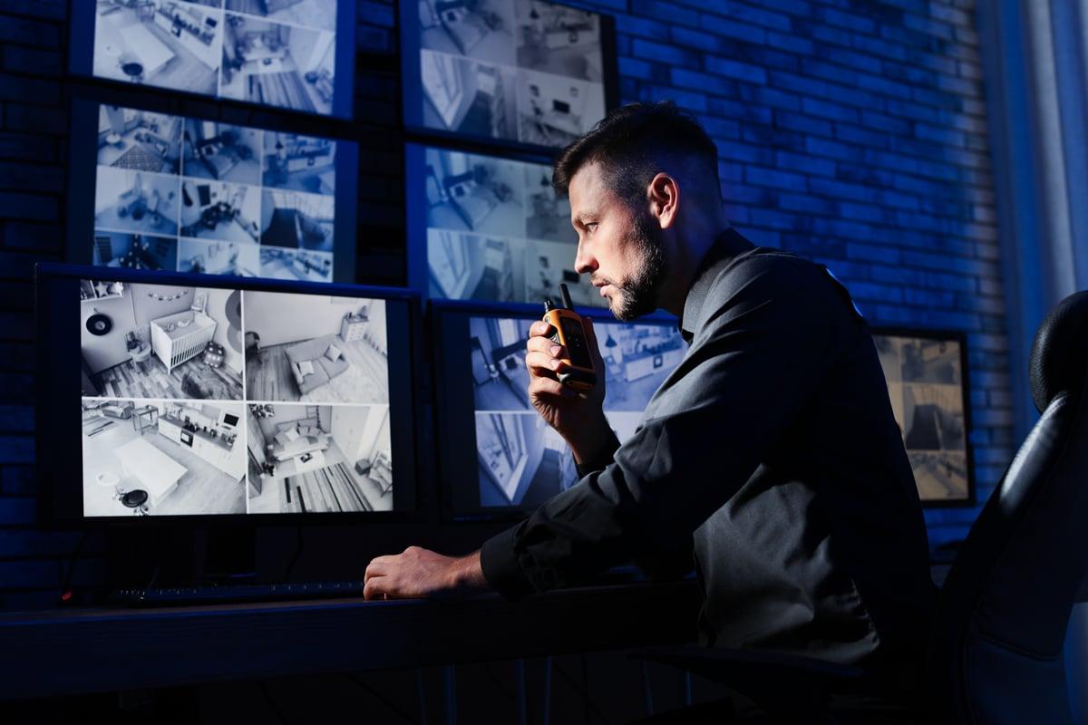 Security worker using walkie talkie to communicate with team in dark security room