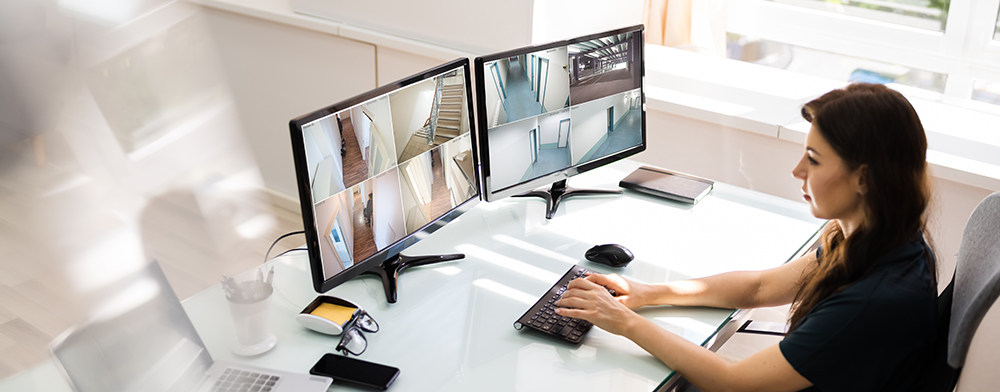 Woman monitoring two security camera monitors in office
