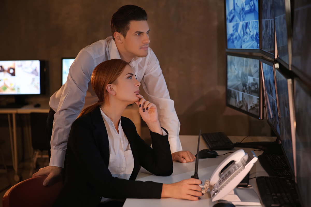 Woman showing man video feed on security monitors