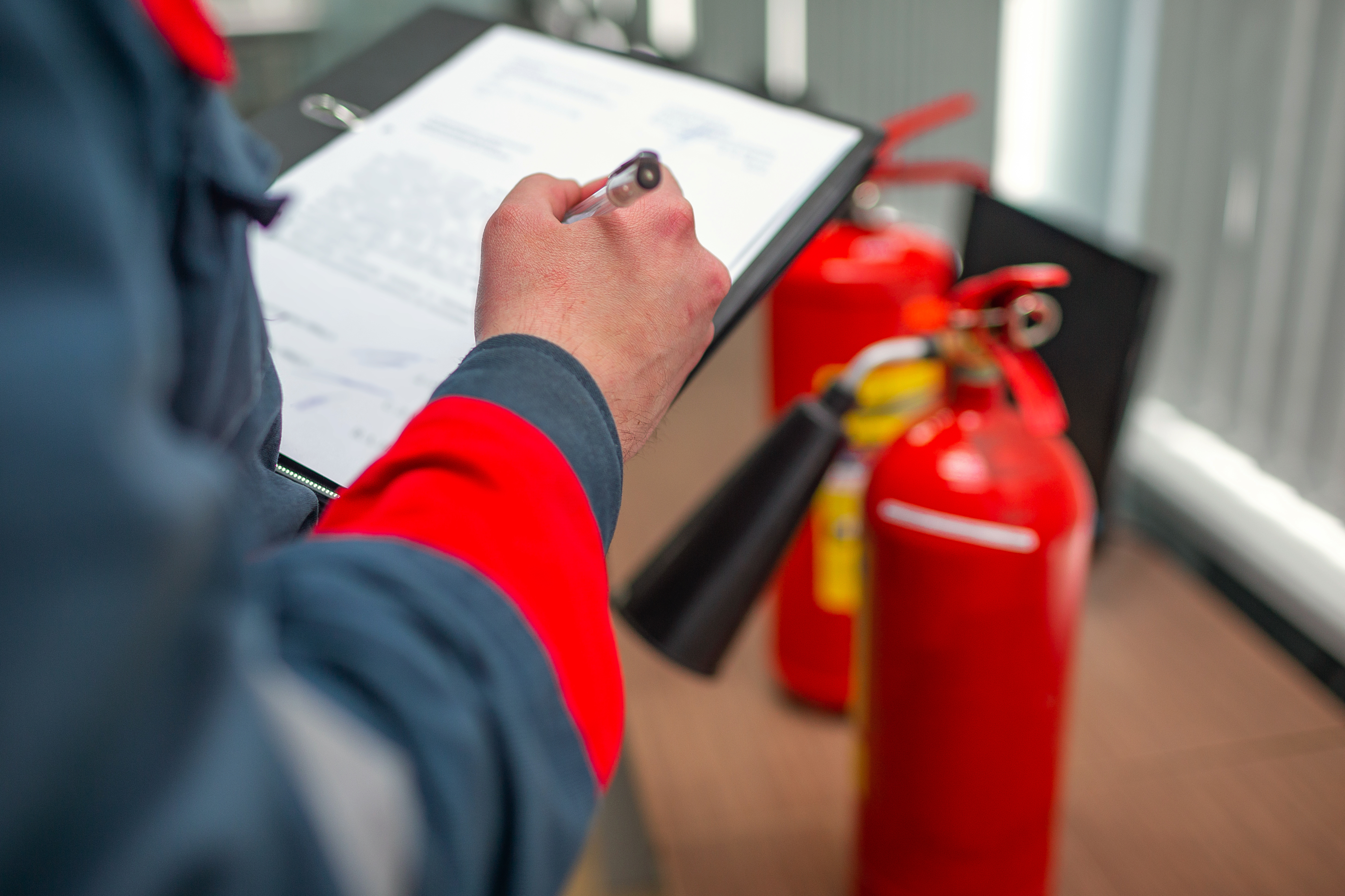 Fire system inspector taking notes on system
