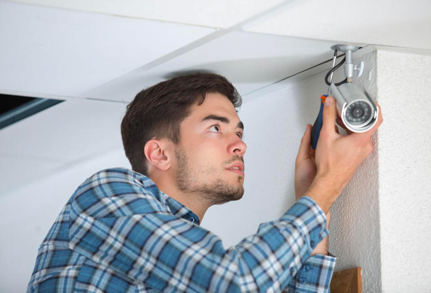 Man installing security camera on ceiling