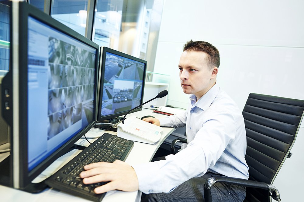 Security worker looking intensely at monitors